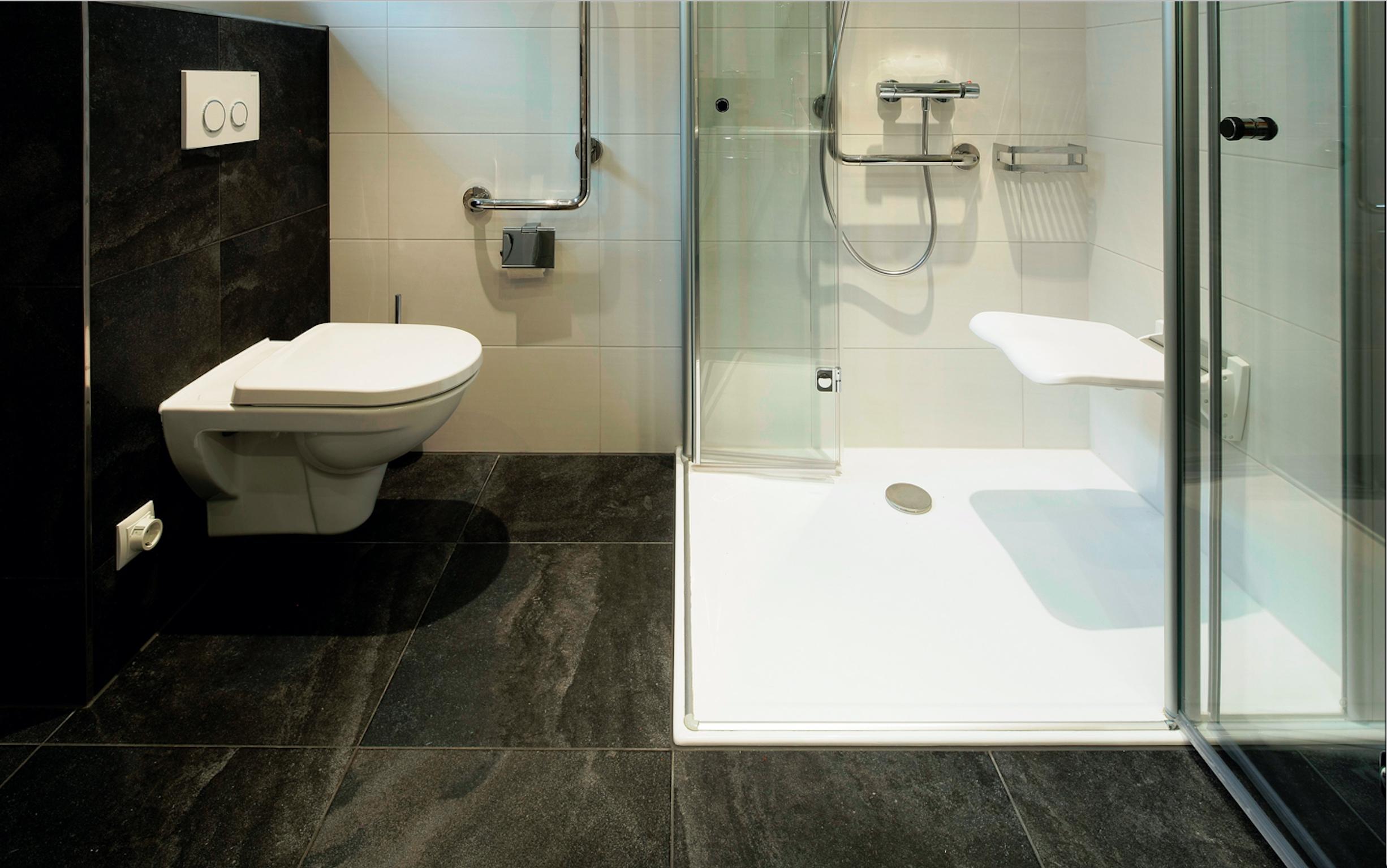 Großzügige Dusche mit Sitzgelegenheit - bad+co